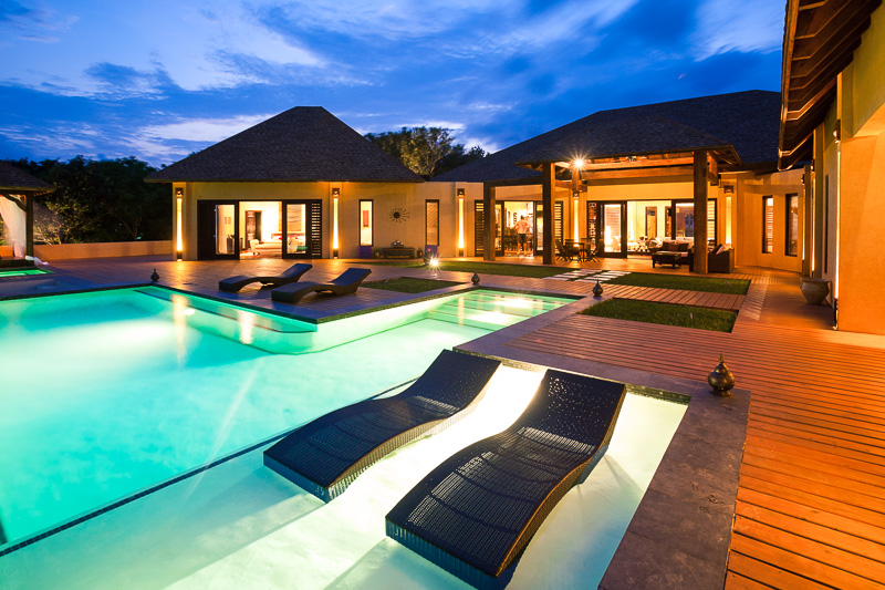 pool and deck with well lit house in background at night
